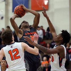 Evanston's Jalen Christian (21) shoots over Oak Park's Charlie Hoehne (14) and Anthony Roberts (23) in Oak Park,  Saturday, February 2, 2019. | Kevin Tanaka/For the Sun Times