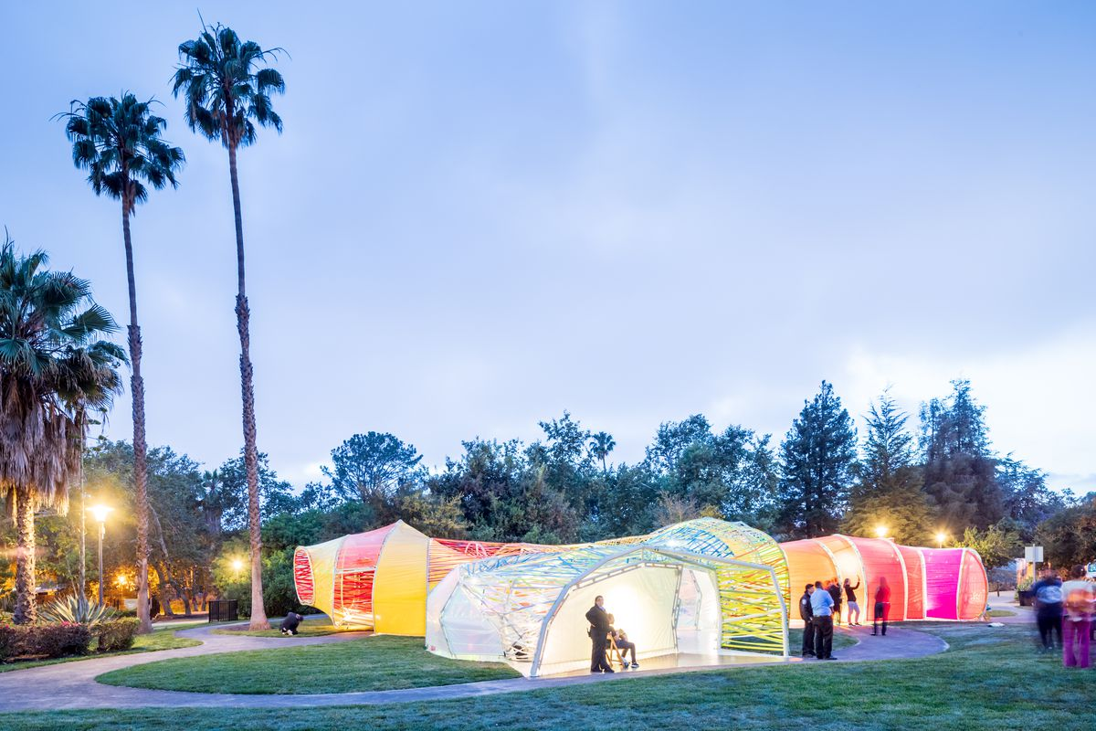 A photo of the glow-worm-like pavilion set up on a lawn at the tar pits.