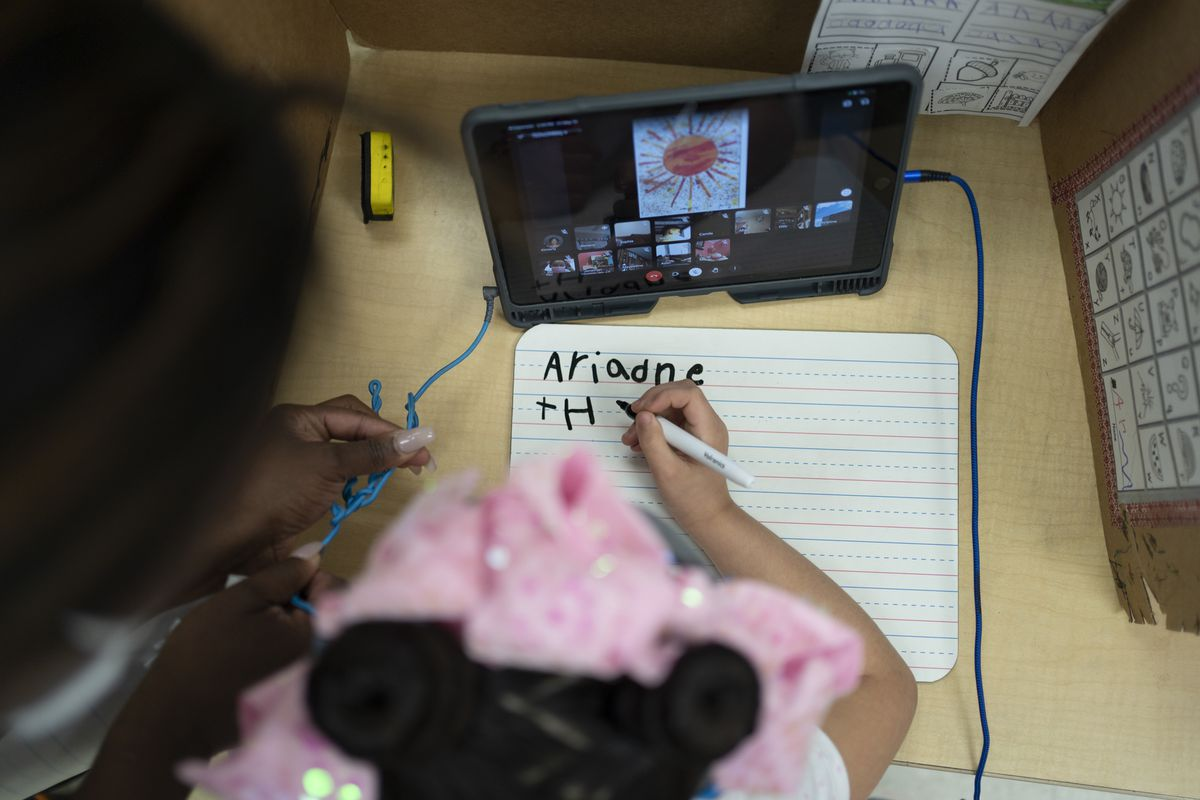 A girl wearing a pink bow works on a writing assignment while a teacher looks over her shoulder. There is a tablet on the desk in front of her.