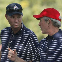 USA's captain Davis Love III talks to former President George W. Bush on the fifth hole during a four-ball match at the Ryder Cup PGA golf tournament Saturday, Sept. 29, 2012, at the Medinah Country Club in Medinah, Ill.
