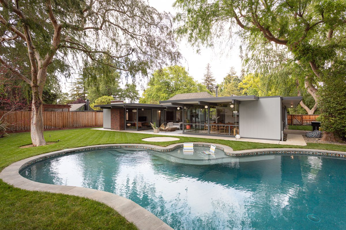 A bulbous-shaped swimming pool next to a grassy lawn in front of a single-story home.