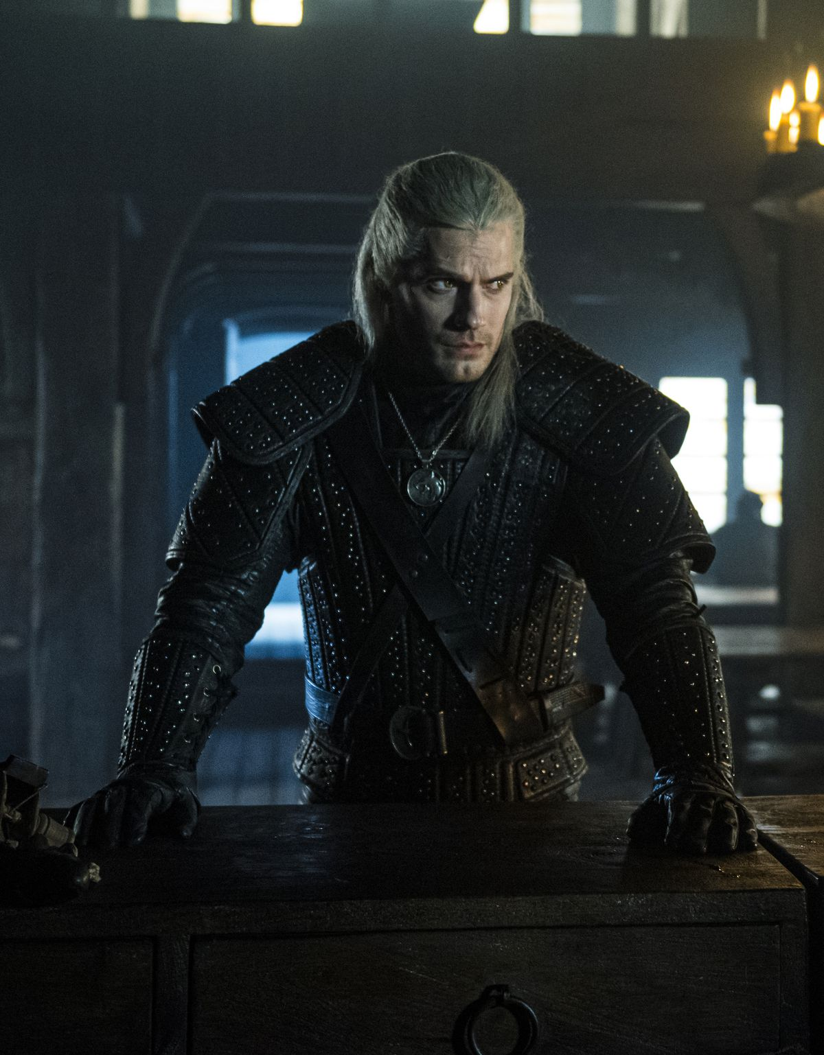 geralt stands with his hands on a table