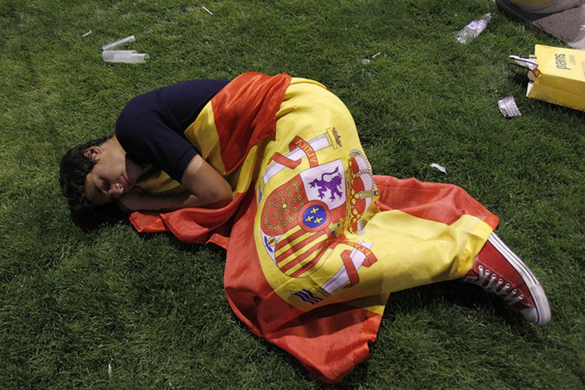 A supporter of the Spanish sleeps with a flag at Paseo Recoletos after the 2010 FIFA World Cup South Africa Final match between Spain and Netherlands on July 11 2010 in Madrid Spain. (Photo by Angel Martinez/Getty Images)