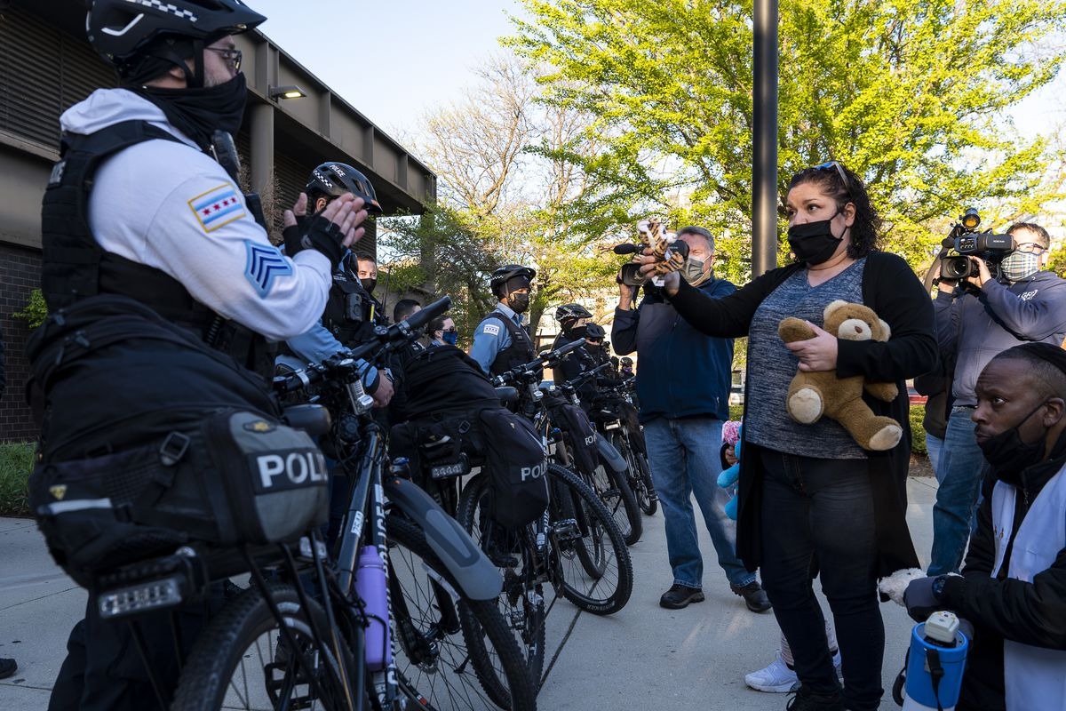 Garciela Garcia offers a Chicago police officer a stuffed animal outside the Chicago Police Department's training facility on Friday.