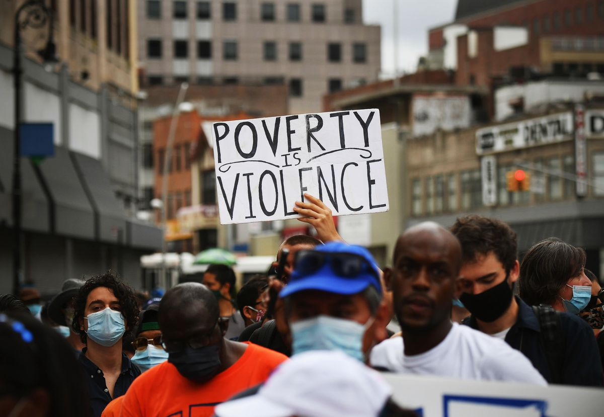 """A group of protesters on an urban street, one of whom holds a sign reading """"Poverty is violence."""""""