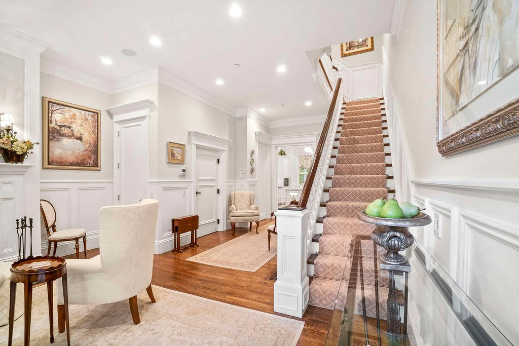 A entry foyer with a sitting area and a long carpeted staircase.
