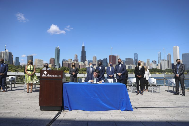 Gov. J.B. Pritzker signs the Climate and Equitable Jobs Act at the Shedd Aquarium on Wednesday.