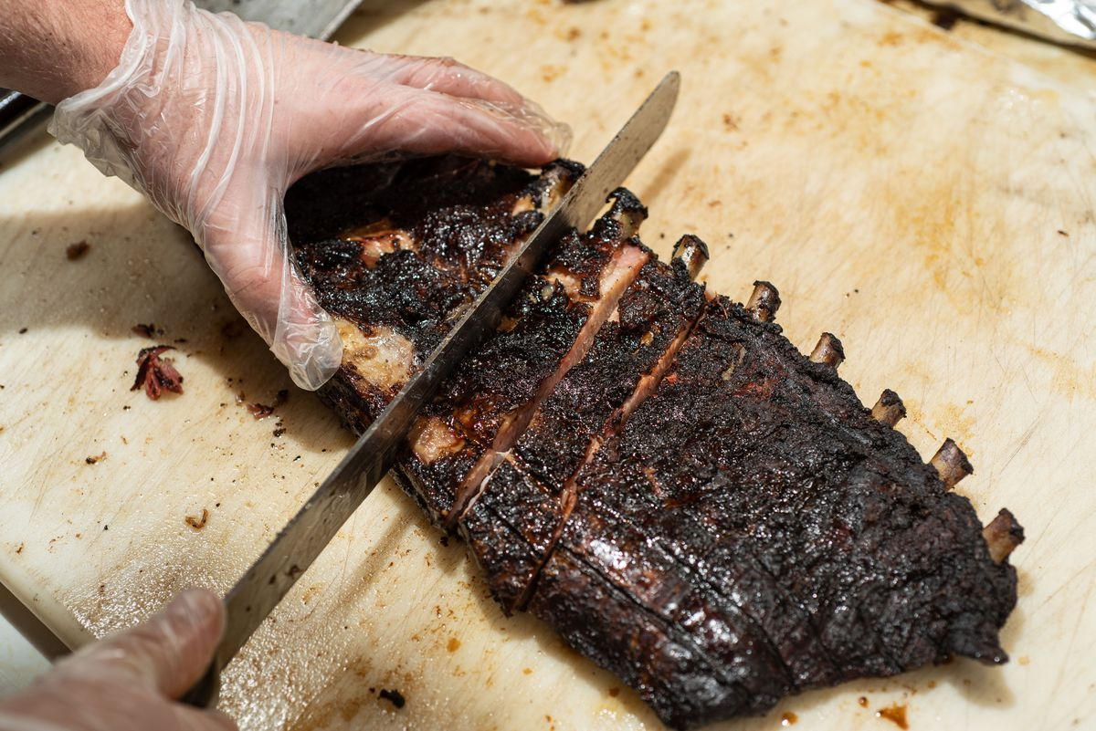 A rack of ribs being sliced with a knife.