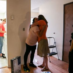 Laura Avalos, center left, embraces Laura Walton as Walton and other volunteers help clean an apartment they found for Avalos's family in Phoenix, Ore., on Monday, Sept. 21, 2020. Avalos and her family lost their home in the Almeda Fire and received help locating housing from a network of women aiming to assist migrant and Latino families impacted by the fire.