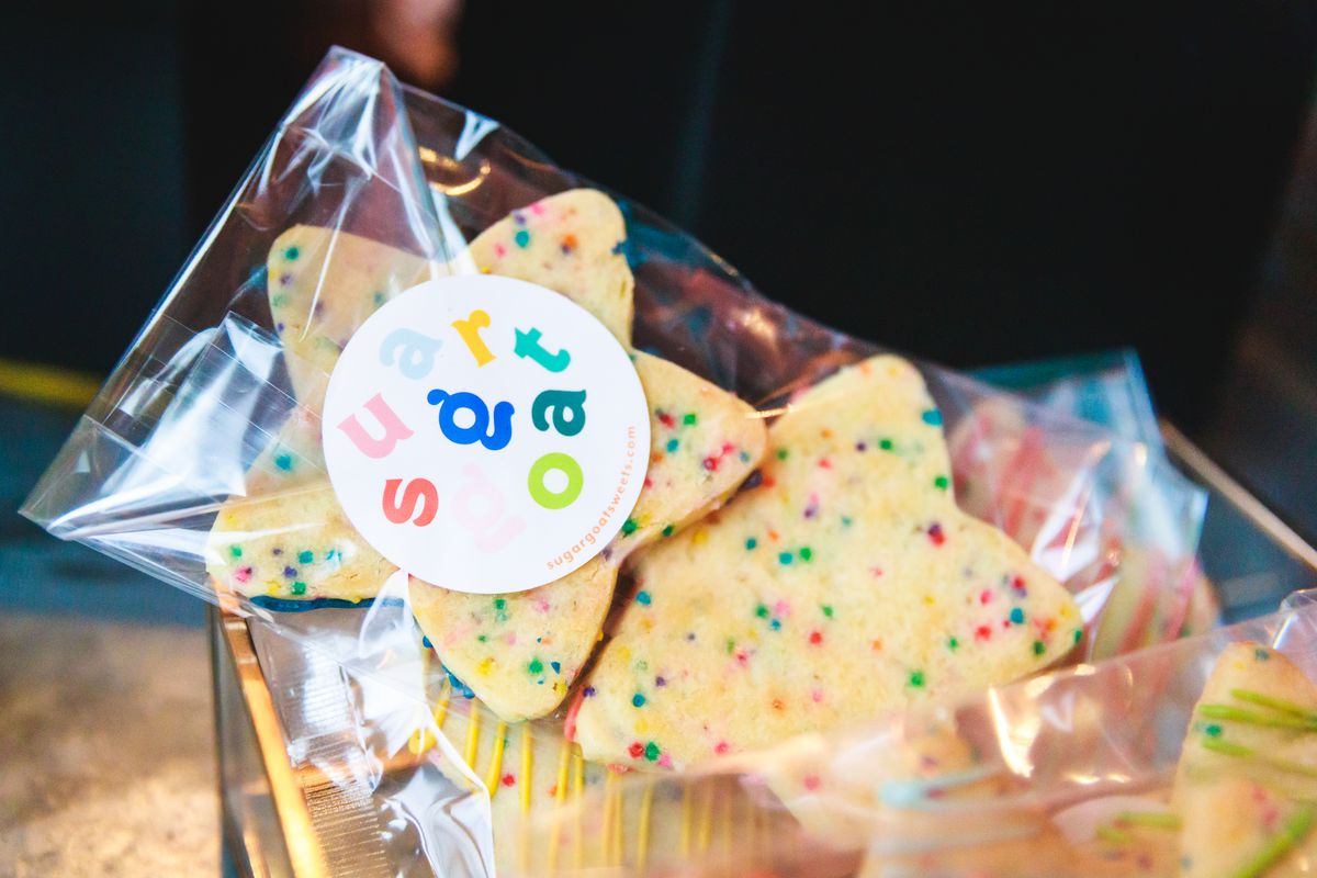 """Two star-shaped cookies with multi-colored sprinkles in a plastic bag. A white sticker on the bag reads """"Sugargoat."""""""