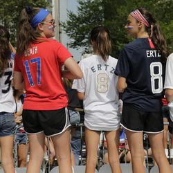 Girls in soccer jerseys wait for the arrival of the U.S. women's soccer team at New York City Hall.