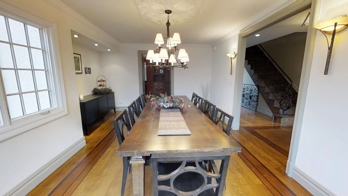 A dining room with a large, rectangular table with several chairs and a chandelier.