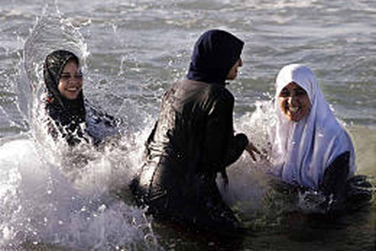 Three Palestinian women swim fully covered in the Mediterranean Sea at Gaza City Friday. Friday is traditional day of prayer and rest.