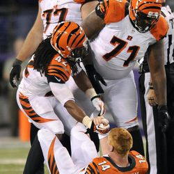 Cincinnati Bengals' BenJarvus Green-Ellis (42) and Andre Smith (71) assist quarterback Andy Dalton after he was sacked by Baltimore Ravens linebacker Ray Lewis in the second half of an NFL football game in Baltimore, Monday, Sept. 10, 2012. Dalton fumbled and Ravens cornerback Lardarius Webb recovered the ball on the play. The Ravens won 44-13.