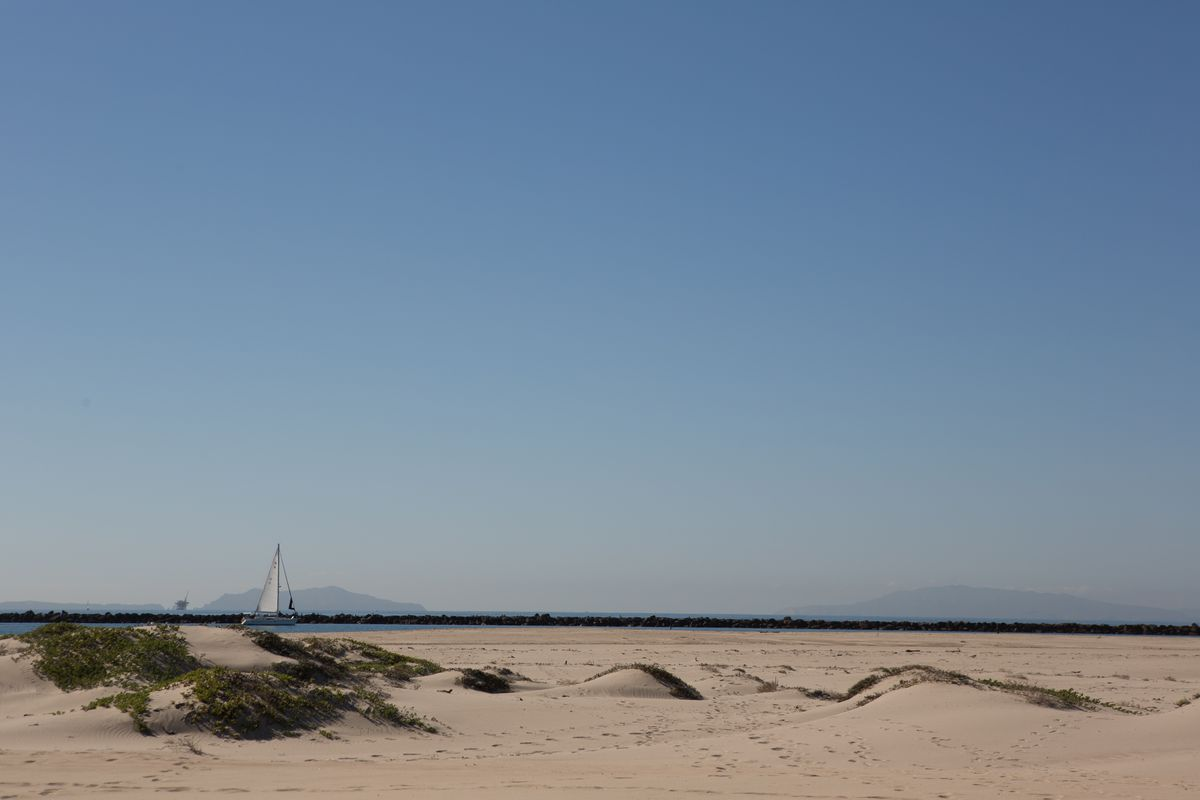 The beach, with a sailboat in the distance.