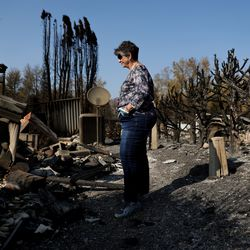 Anne Noble looks at the remains of the home she shared with her husband, Bob, in Talent, Ore., while giving journalists a tour on Saturday, Sept. 19, 2020. Their home was one of more than 2,300 residences destroyed when the Almeda Fire swept through the towns of Talent and Phoenix in southern Oregon.