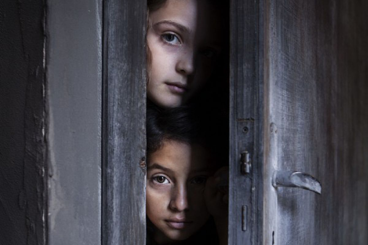 Elisa Del Genio as Elena Greco (top) and Ludovica Nasti as Lila Cerullo (bottom) looking through a crack in a door in a still from HBO's My Brilliant Friend