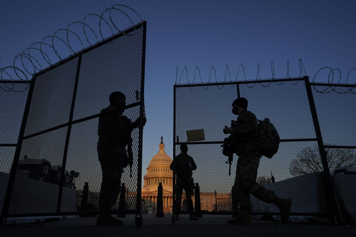 Members of the National Guard open a gate in the razor wire topped perimeter fence around the Capitol at sunrise in Washington on March 8.