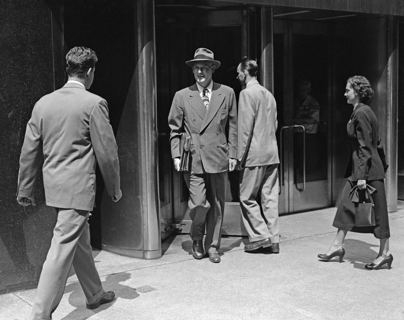 A black-and-white photo taken in the 1950s of three men and one woman walking in and out of the revolving door of an office building. All are wearing suits.