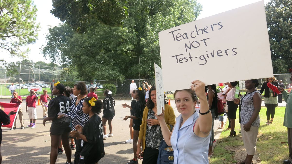 A former teacher raises a sign contesting some of Duncan's favored policies.
