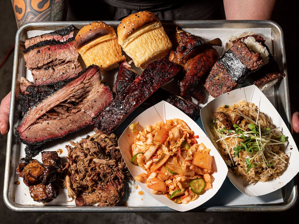 Two hands hold a large tray of smoked meat including brisket, photographed from above.
