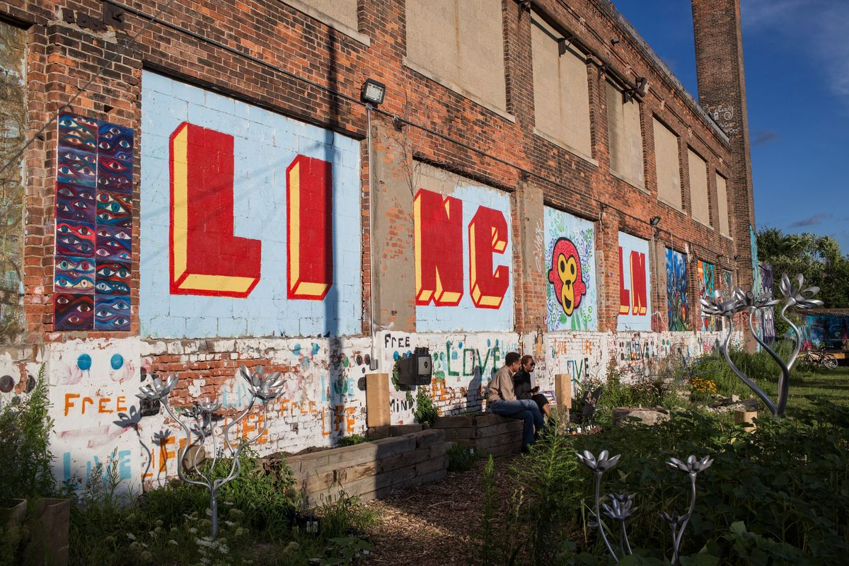The exterior of a building. There is a mural on the side of the building with the word: Lincoln.