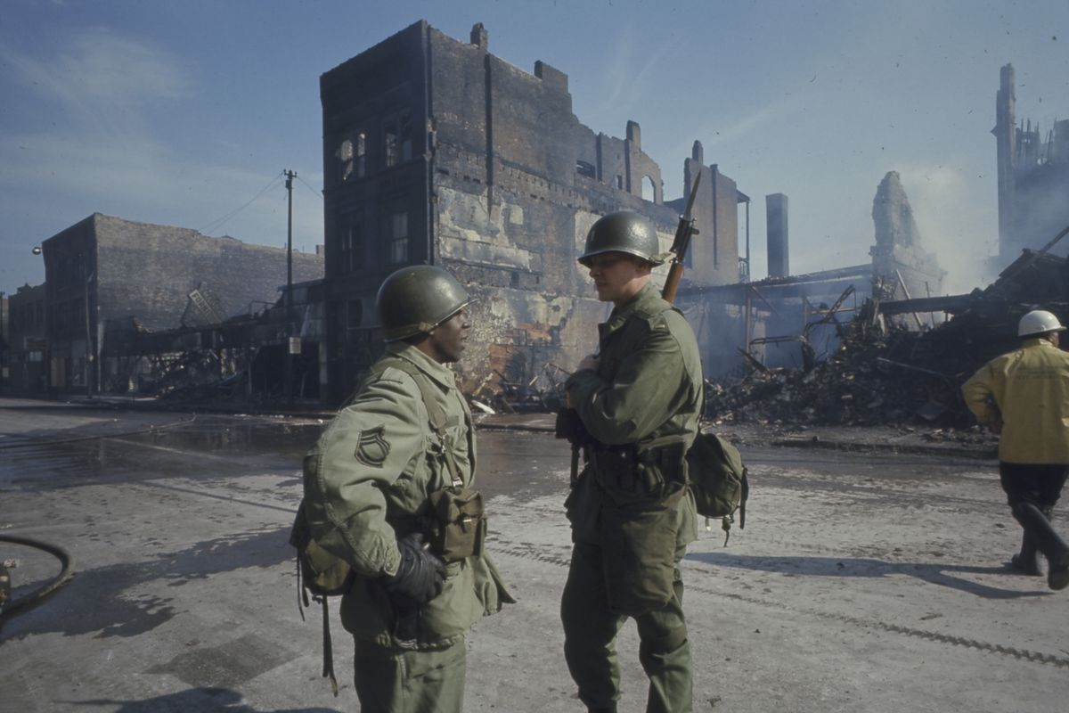 National Guard in front of burning buildings