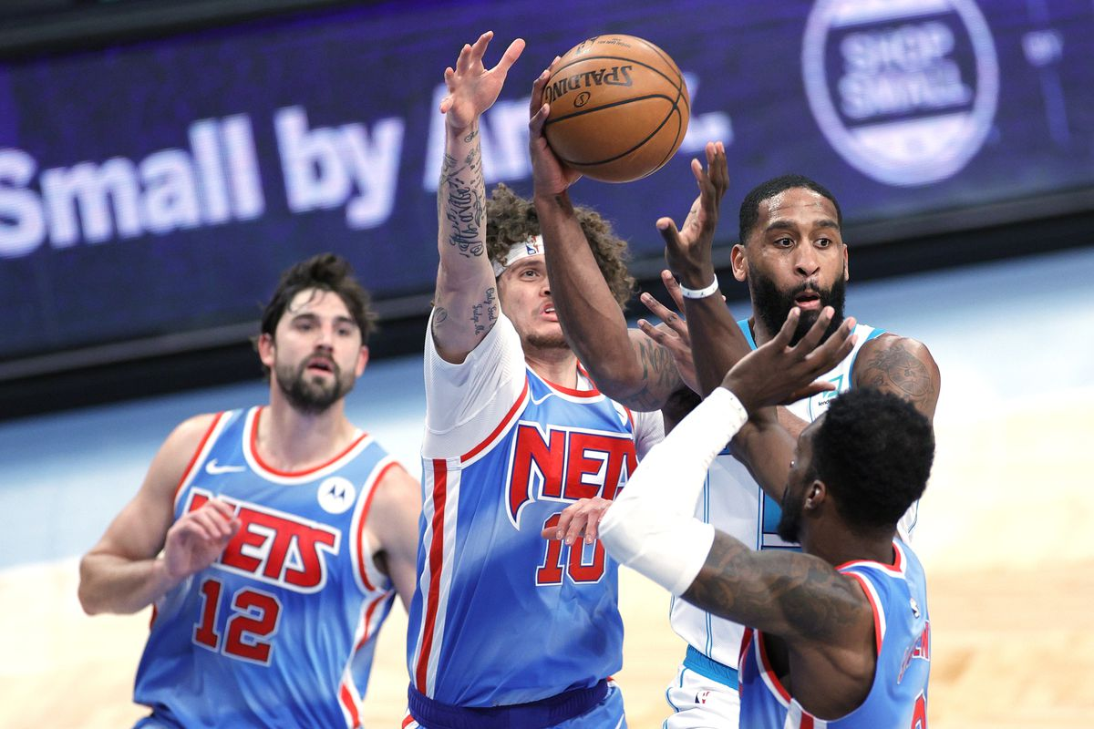 Brad Wanamaker #9 of the Charlotte Hornets passes the ball as Joe Harris #12, Tyler Johnson #10, and Jeff Green #8 of the Brooklyn Nets defend during the second half at Barclays Center on April 01, 2021 in the Brooklyn borough of New York City. The Nets won 111-89.
