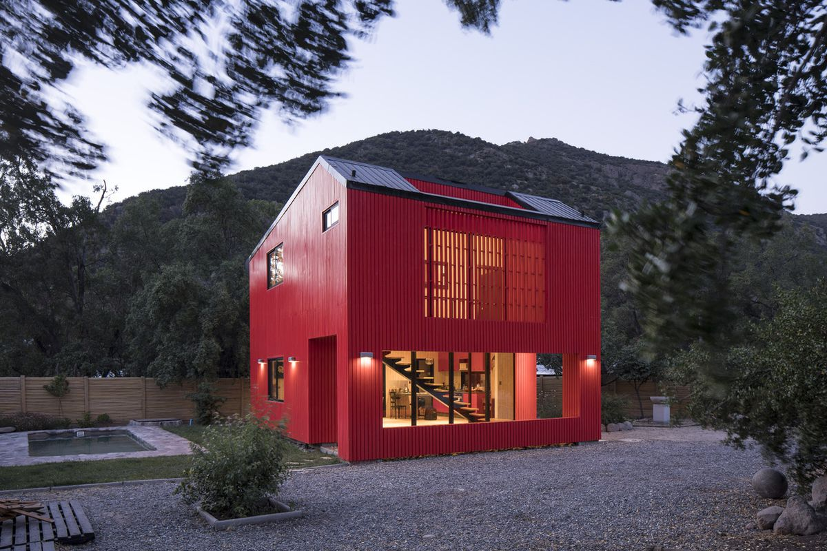 Outside of red prefab house at dusk