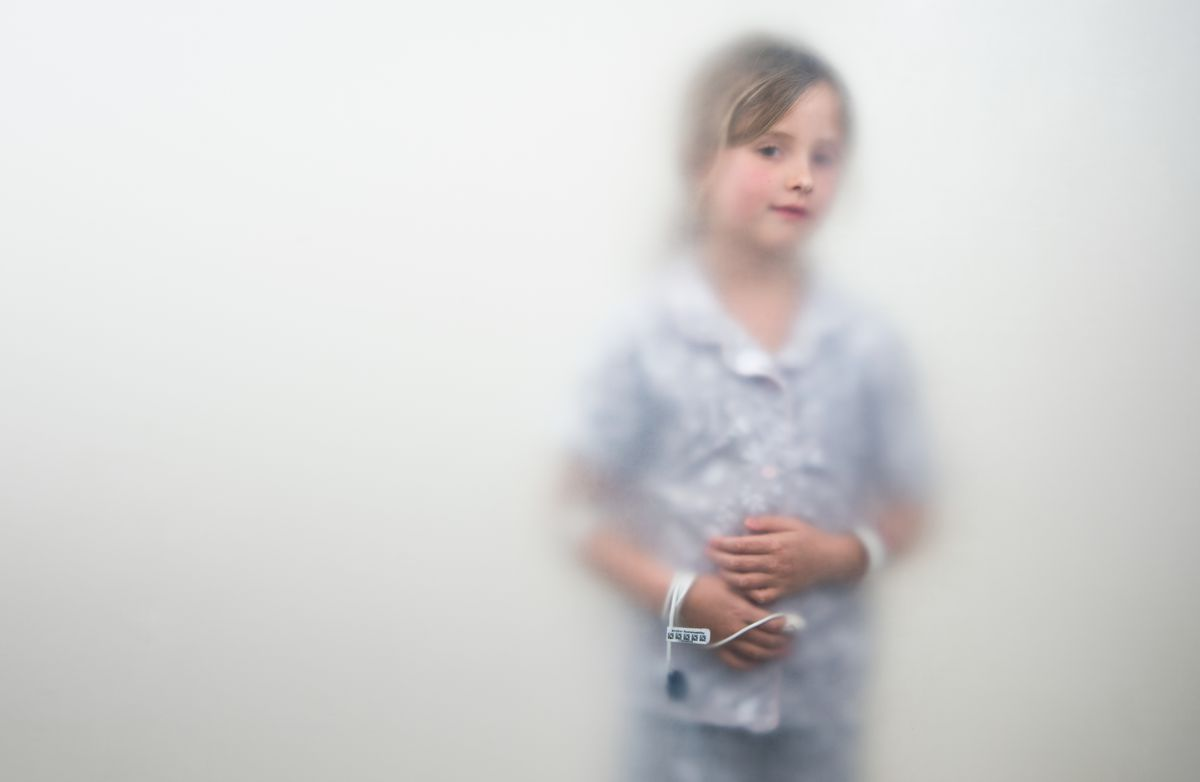 Youngish girl (11?) in white shirt and pants with white wristbands on arms and something taped to her fingertip connected to something on her wrist, probably a medical device