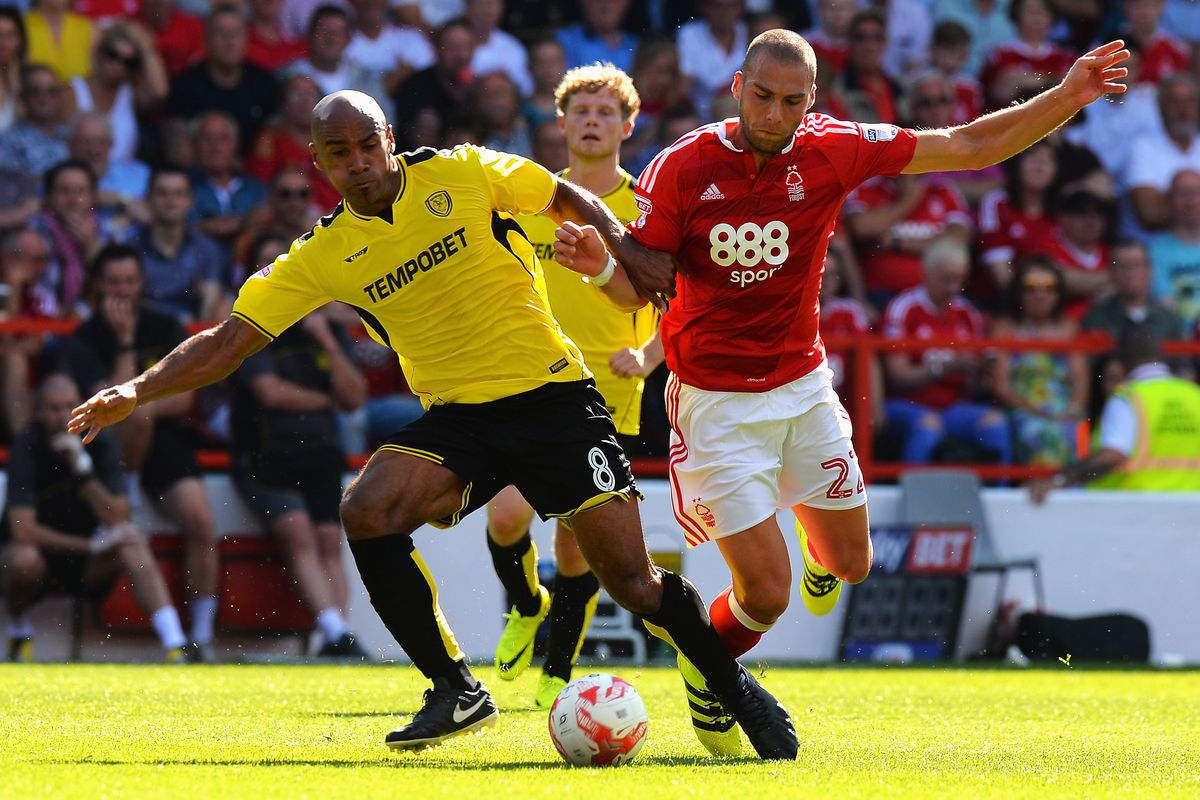Chris O'Grady of Burton Albion tackles Pajtim Kasami of Nottingham Forest during the Sky Bet Championship match between Nottingham Forest and Burton Albion at City Ground on August 6, 2016 in Nottingham, England.