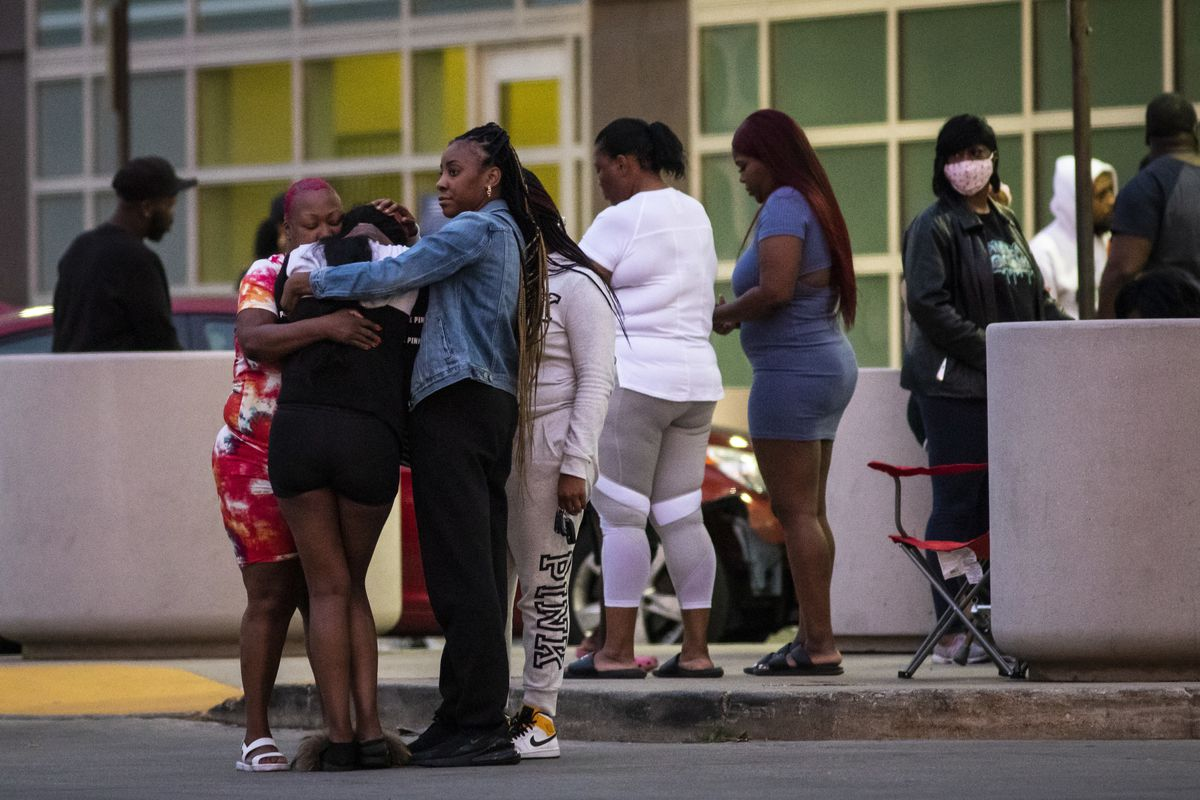 Mourners hug and cry as hundreds gather in the parking lot of Stroger Hospital after a 40-year-old man was shot to death on the West Side on Memorial Day.