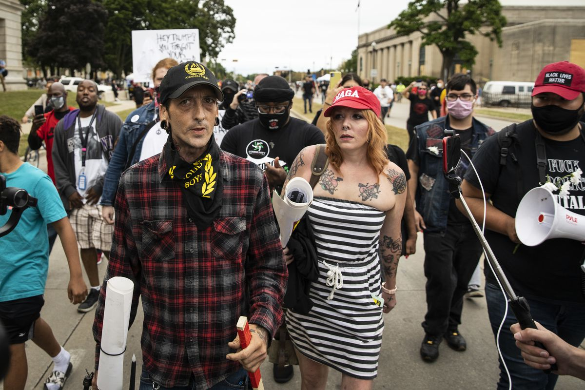 A member of the Proud Boys, a far-right extremist organization, and a woman wearing a MAGA hat are pursued by Black Lives Matter protesters after an argument outside the Kenosha County Courthouse, Tuesday evening.