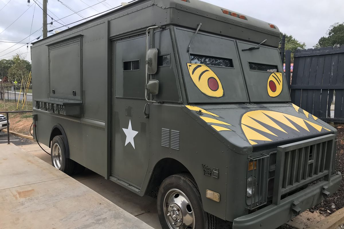 The army green Gaja Korean food truck with painted yellow eyes and teeth parked next to the patio