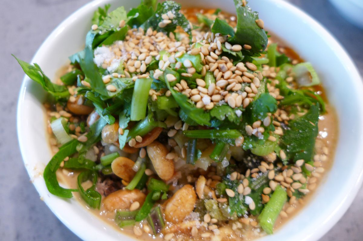 A bowl of chunky sauce strewn with sesame seeds and fresh cilantro...