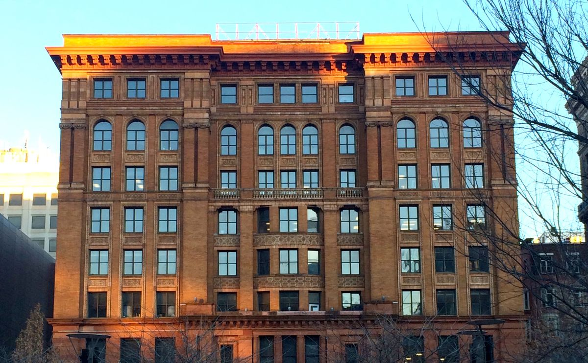 The exterior of the Bourse Building in Philadelphia. The facade is brown brick with a flat roof and multiple windows.
