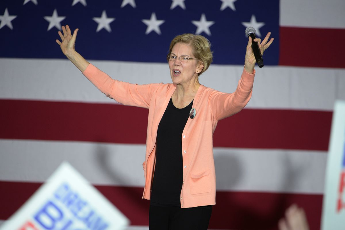 Elizabeth Warren with her hands in the air on stage at a campaign rally with the American flag behind her.