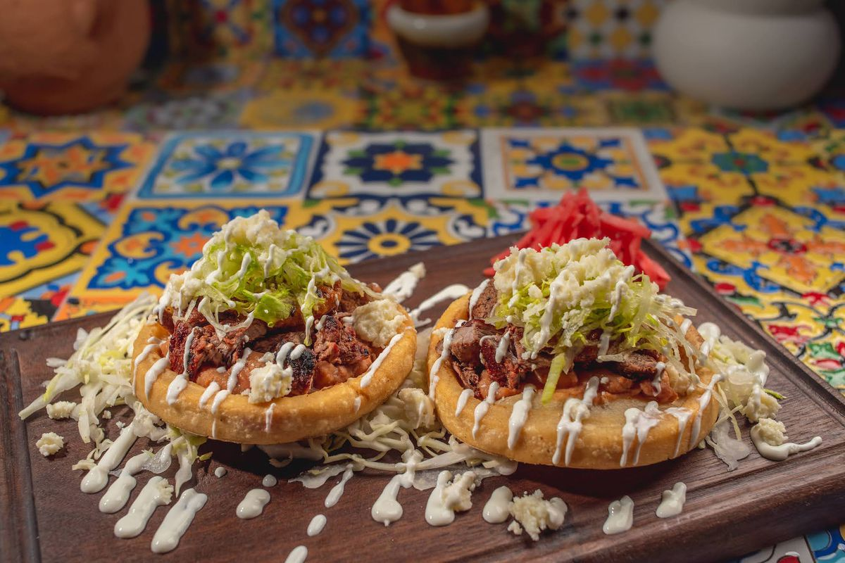 A side-angle view of two sopes with meat and a drizzle of sauce on a wooden board.