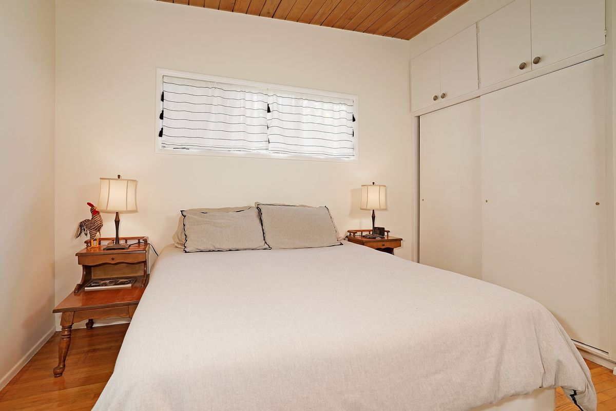 A bedroom with white walls and closet doors.
