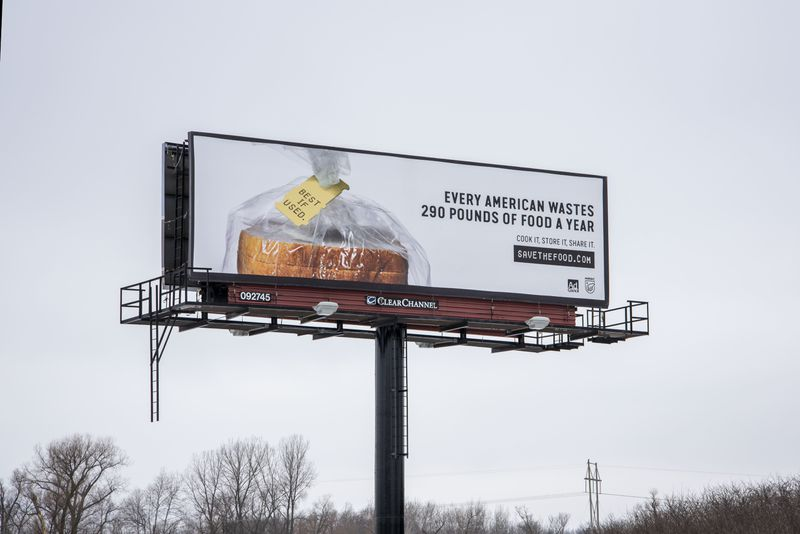 """A billboard with a picture of a bagged loaf of bread reads, """"Every American wastes 290 pounds of food a year. Cook it, Store it, Share it. Savethefood.com."""" The tag on the bread reads, """"Best if used."""""""
