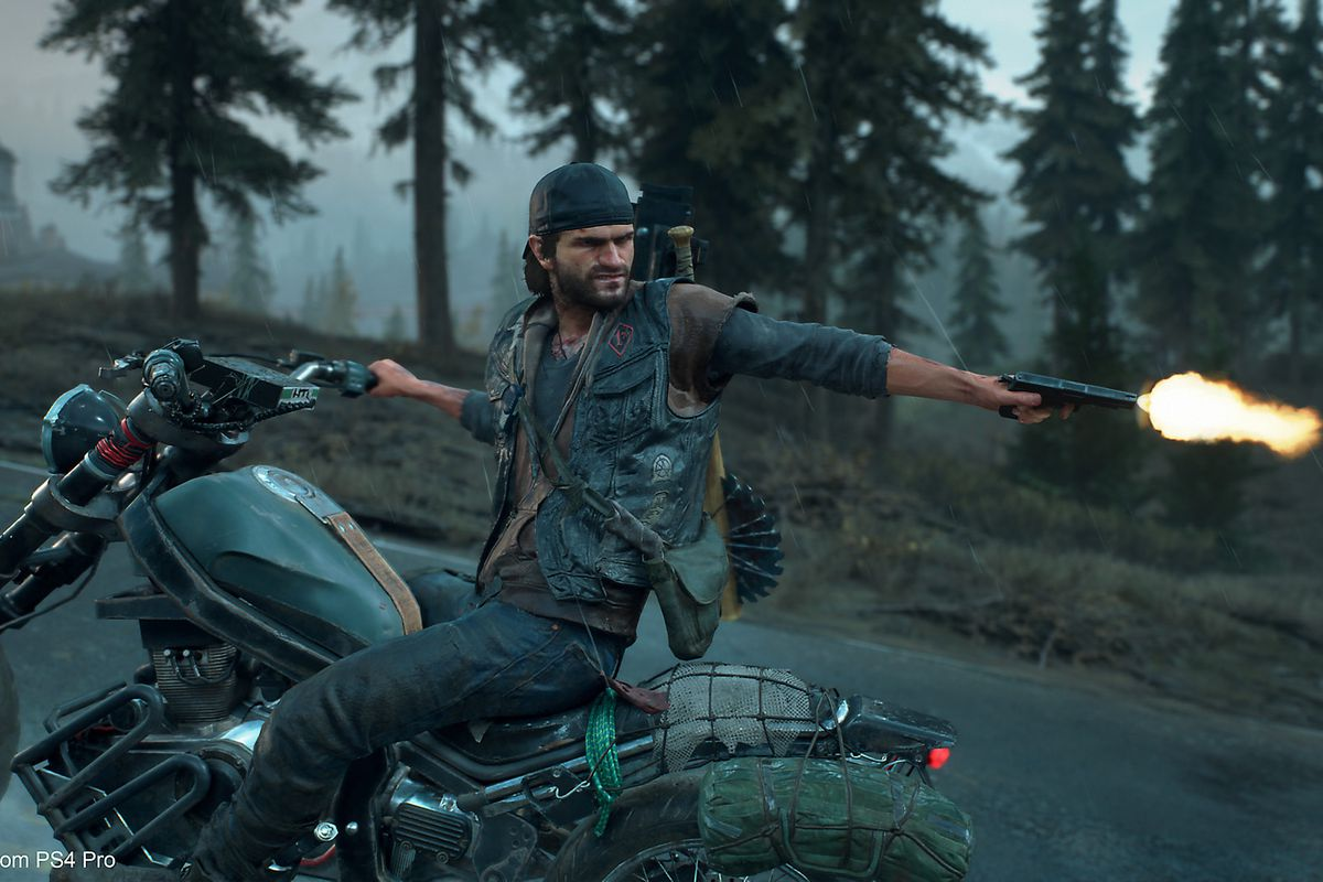 A man rides a motorcycle while turning around to shoot at something behind him