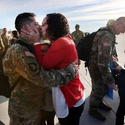 Carla Vargas kisses her husband, Sgt.  Abel Vargas, as soldiers from Detachment 2, 101st Airborne Division (Air Assault) return to Utah on Friday, Nov. 18, 2016, following an 11-month deployment to Iraq. Behind them is their daughter Karina.