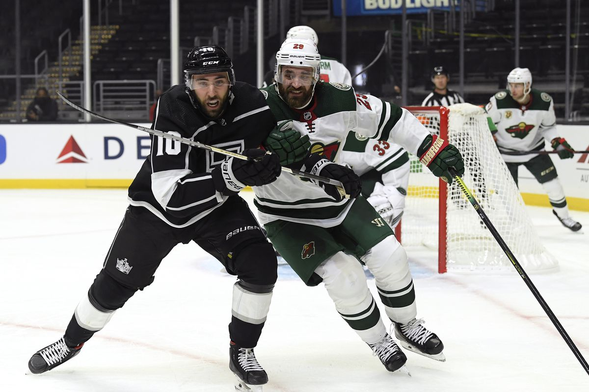 Michael Amadio #10 of the Los Angeles Kings and Greg Pateryn #29 of the Minnesota Wild skate after the puck during a 4-3 Wild overtime win in the season opening game at Staples Center on January 14, 2021 in Los Angeles, California.