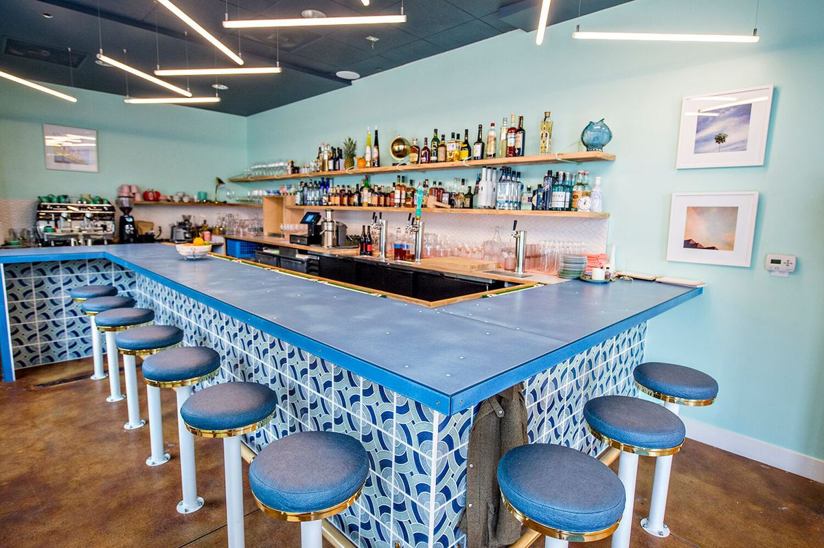 A blue bar and stools with shelves with drinks visible behind it at Somebody People