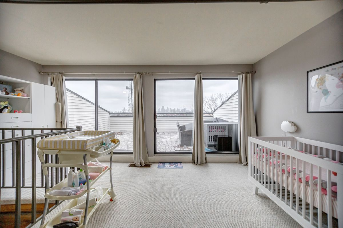 A carpeted room with a baby crib and windows facing a deck.