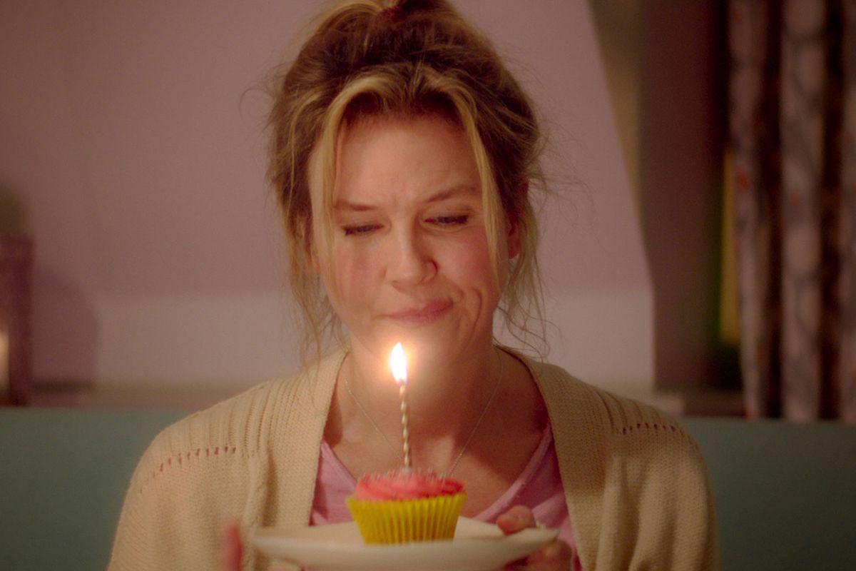Bridget Jones makes a face at a birthday cupcake