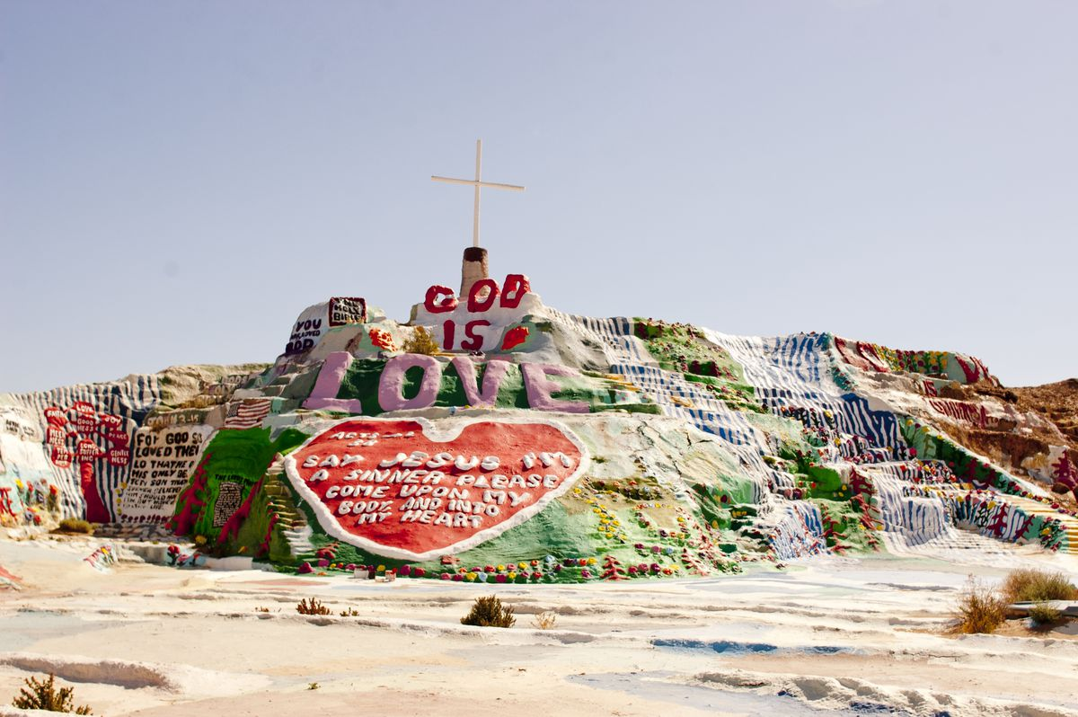 A mountain in the desert that has colorful art on it.