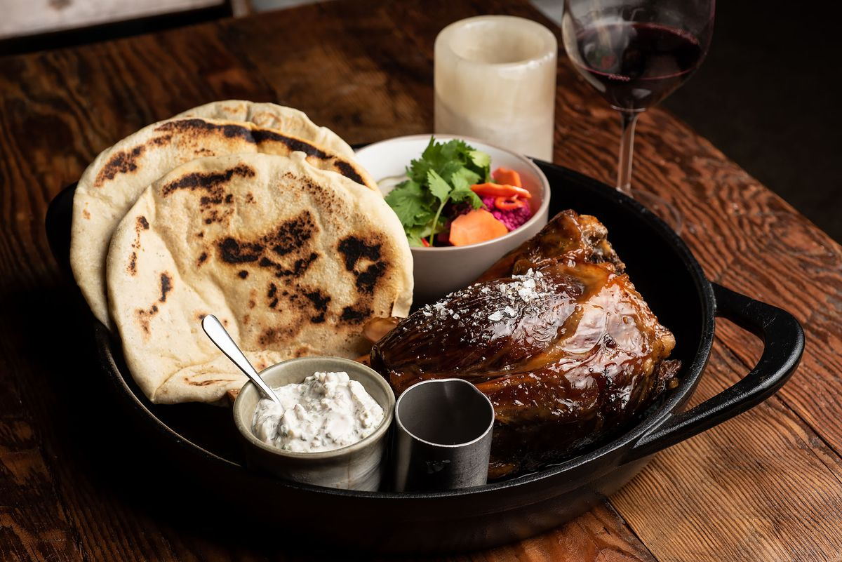 A large roasted leg of beef with side pita, in a cast iron skillet, and wine and a candle beyond.
