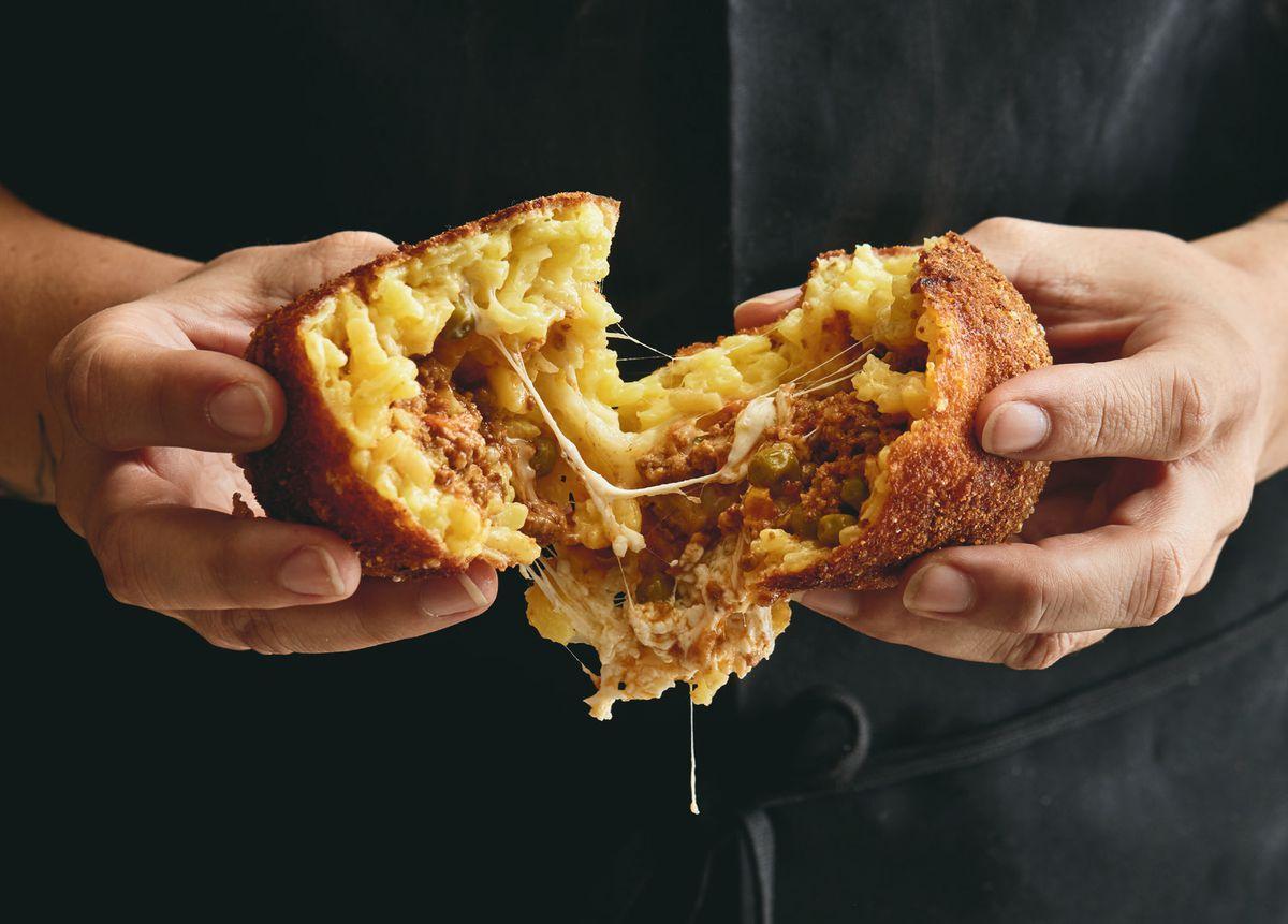 hands breaking apart arancini