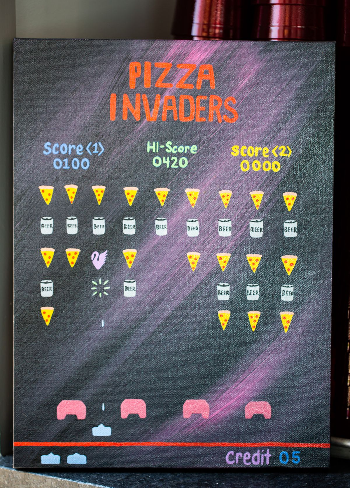 Hand painted pizza invaders poster in the bathroom